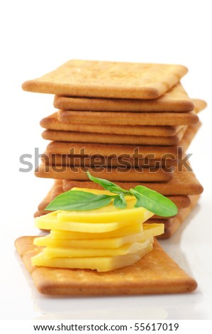 Stack of square crackers with slices of cheese and basil isolated on white background.