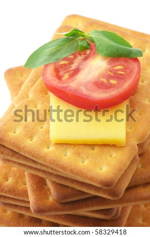 Stack of square crackers with slices of cheese, tomato and basil close-up on white background. - stock photo