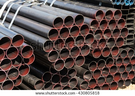 Stack of steel pipes at construction site - stock photo