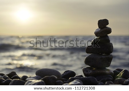 Stack of stones on beach. Sea, sun and sky. - stock photo