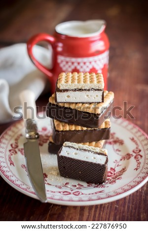 Stack of sugar cookies with marshmallow and chocolate glaze and a pot of fresh milk for breakfast - stock photo