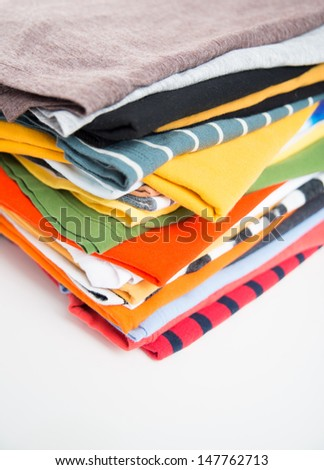Stack of T-shirts and Clothes on White Background