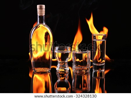Stack of tequila on fire. Red burning pepper in a glass with alcohol also burns with fire in black background - stock photo