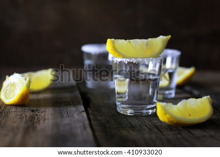 stack of tequila with salt and lemon on a wooden background - stock photo