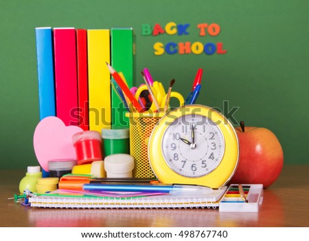 Stack of textbooks, stationery set alarm clock and an apple on a green background.