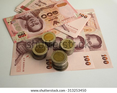 Stack of Thai coins on bank notes money background