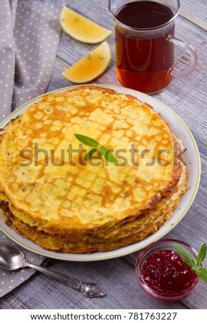 Stack of thin pancakes, crepes on white plate, cup of tea and berry jam