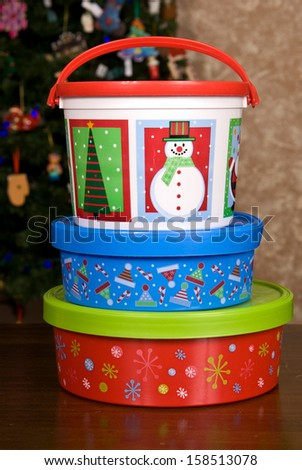 Stack of three Christmas Holiday Cookie Containers sitting on a wooden table top in front of a Christmas tree. - stock photo