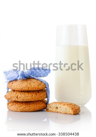 Stack of three homemade oatmeal cookies tied with blue ribbon in small white polka dots, half of cookie and glass of milk, isolated on white background