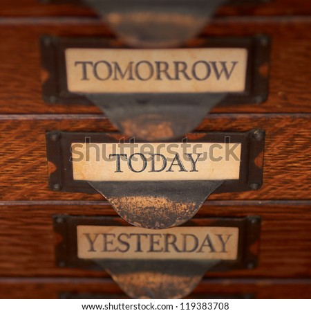 """Stack of three old, oak flat file drawers with """"Yesterday"""", Today, and """"Tomorrow"""" printed on tags in tarnished brass label holders. Shallow depth of field with focus on """"Today"""". - stock photo"""