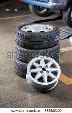 Stack of tires and hubcap at auto repair shop - stock photo