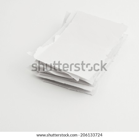 Stack of torn into parts paper pieces over white surface
