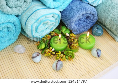 Stack of towels, candles, stones on mat background.
