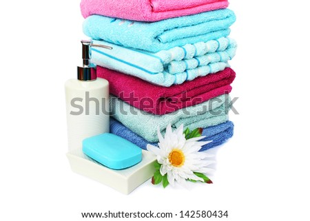 Stack of towels, soaps and flowers isolated on white background. - stock photo