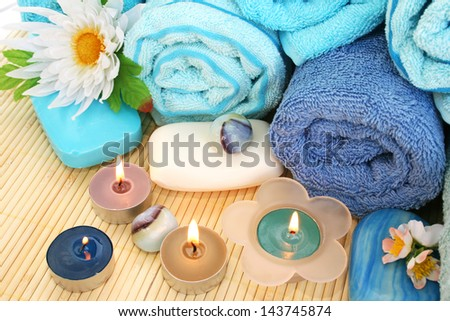 Stack of towels, soaps, candles, stones, flowers on mat background. - stock photo