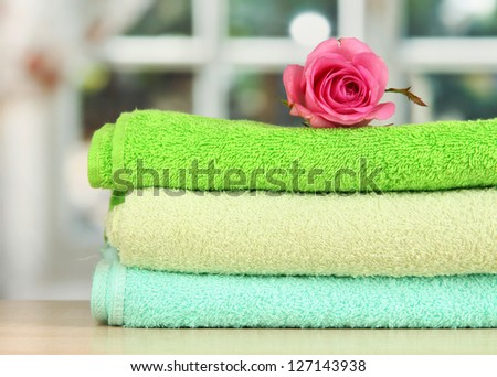 Stack of towels with fragrant flower on window background