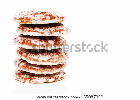 stack of traditional christmas lebkuchen gingerbread cookies with sugar icing on white background - stock photo