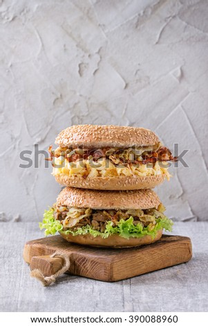 Stack of Two Bagels with stew beef, fresh salad, bacon, scrambled eggs and fried onion served on small wooden chopping board over white wooden table.  - stock photo
