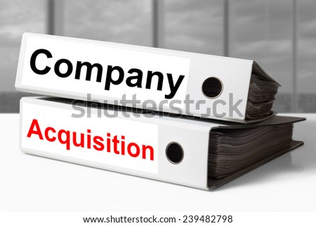 stack of two white office binders company acquisition - stock photo