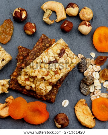 Stack of Useful Granola Bars with Muesli, Nuts and Dried Apricots closeup on Black Stone background. Top View - stock photo