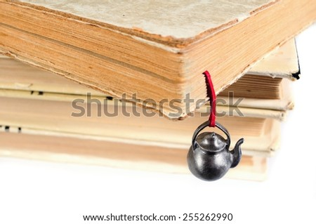 Stack of various used books with an original hand-made bookmark in the form of teapot - stock photo
