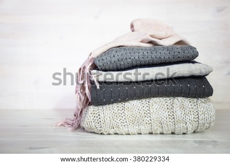 stack of various woolen sweaters on a white wooden background - stock photo