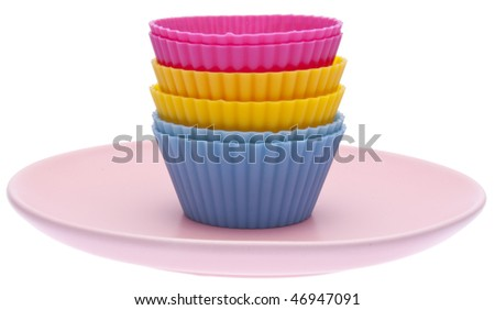 Stack of vibrant cupcake wrappers on a pastel colored plate.  Isolated on white with a clipping path.