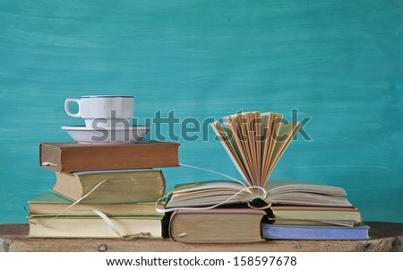 stack of vintage books, coffee cup, free copy space - stock photo