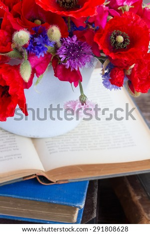 stack of vintage old books  on table with field flowers close up - stock photo