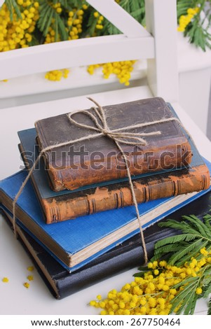 stack of vintage old books  with mimosa flowers - stock photo