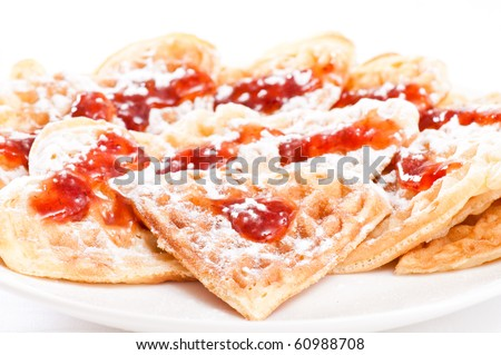 Stack of waffles in shape of heart with strawberry jam and powdered sugar on plate - stock photo