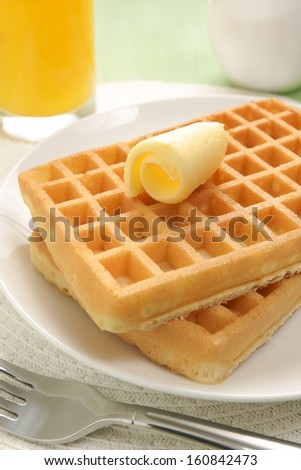 Stack of waffles with a curl of butter and orange juice