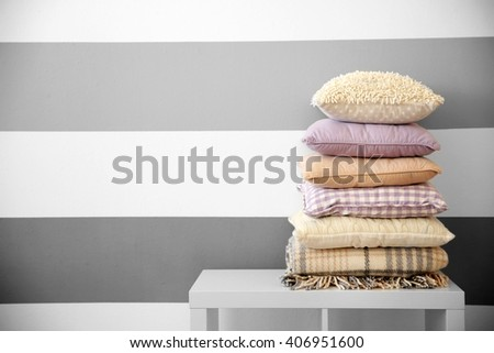 Stack of warm plaid and pillows on white shelf against striped wall background - stock photo