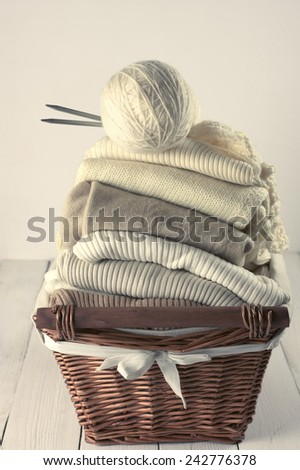 Stack of warm sweaters in basket on white wood. Toned image. - stock photo