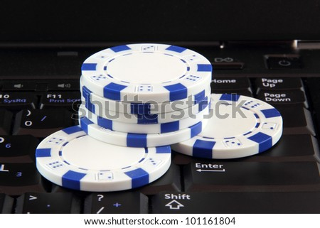 stack of white casino gambling chips on keyboard, online gaming concept - stock photo