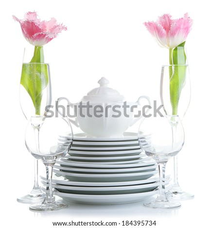 Stack of white ceramic dishes and flowers, isolated on white - stock photo