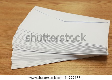 stack of white envelopes on a wooden table - stock photo
