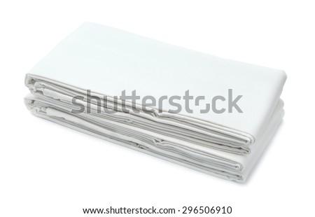 Stack of white folded bedding isolated on white - stock photo