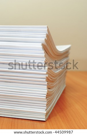 Stack of white journals in office desktop. Shallow deep of field