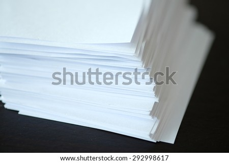 Stack of white paper on the black table.