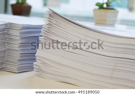 Stack of white papers sheet was organized  on office background.