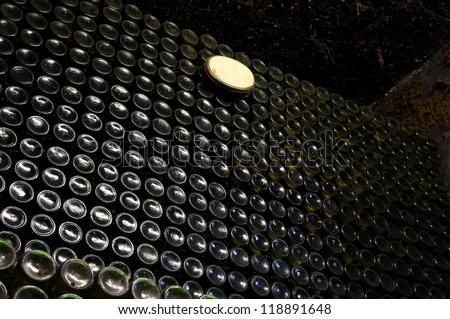 Stack of wine bottles in wine cellar - stock photo