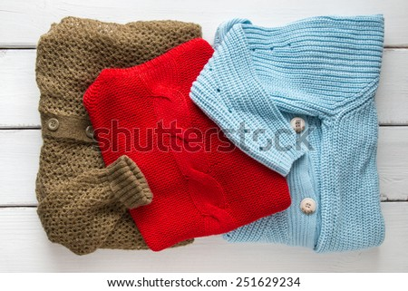 Stack of women's knitted sweaters and cardigans. - stock photo