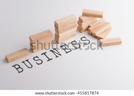 Stack of wood block in statistics graph shape failed and falling down in the end with text BUSINESS, business concept metaphor to failure or destruction in the end. Selective focus, gray background.