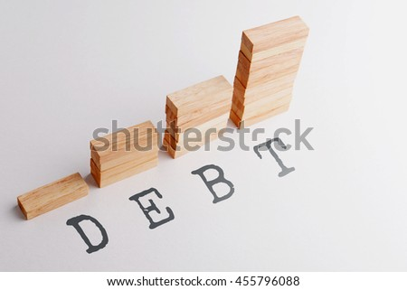 Stack of wood block in statistics graph shape with text DEBT. Business concept in rising and growing debt. Selective focus, gray background. - stock photo