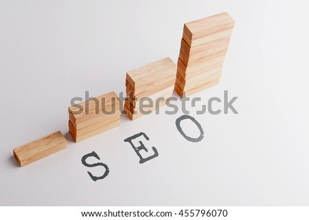 Stack of wood block in statistics graph shape with text SEO, abbreviation of Search, Engine, Optimization. Business concept in rising and growing SEO. Selective focus, gray background. - stock photo