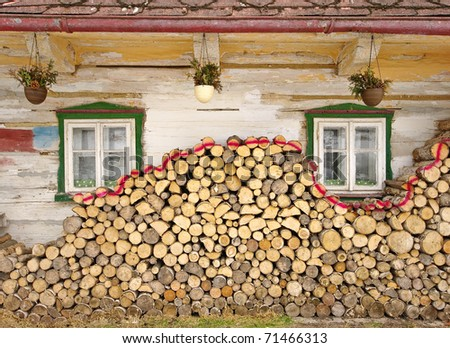 Stack of wood near old cottage windows - stock photo