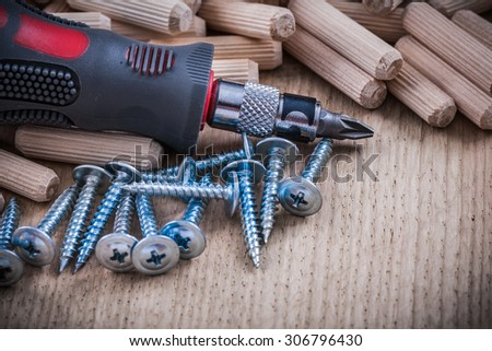 Stack of wooden dowel pins steel nails and insulated turnscrew.