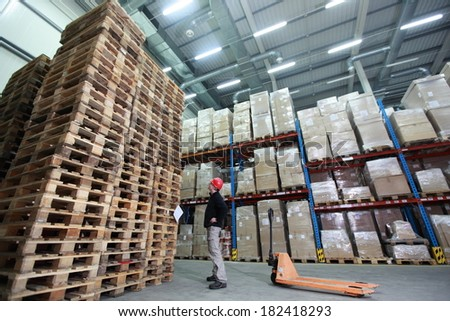 stack of wooden pallets in storehouse - 	worker with hand pallet truck preparing delivery