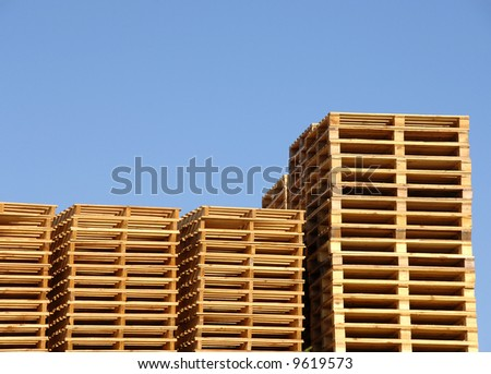 Stack of wooden shipping pallets in warehouse - stock photo